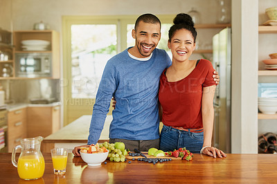 Buy stock photo Portrait of a happy young couple preparing a healthy snack together at home