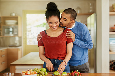 Buy stock photo Shot of a young man kissing his wife while she prepares a healthy snack at home