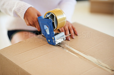 Buy stock photo Shot of an unidentifiable young woman packing boxes while moving house