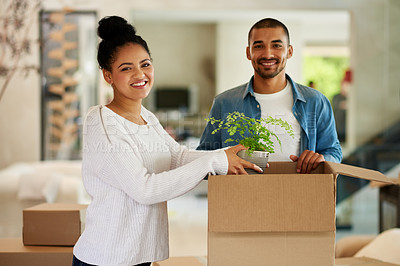 Buy stock photo Portrait of a happy young couple unpacking boxes in their new home together