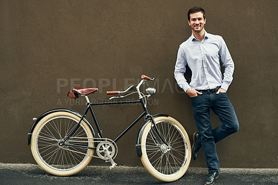 Buy stock photo Portrait of a young man posing with his bicycle against a dark wall