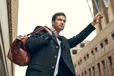 Buy stock photo Cropped shot of a young businessman gesturing to get a cab in the city