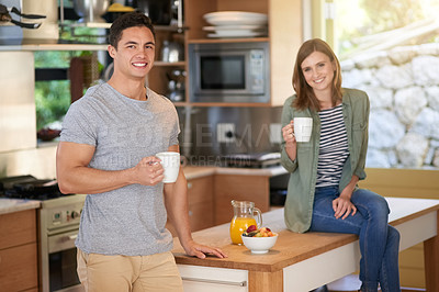 Buy stock photo Portrait of a happy young couple drinking coffee in their kitchen together