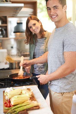Buy stock photo Portrait of a happy young couple cooking a meal together in their kitchen