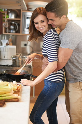 Buy stock photo Shot of an affectionate young couple cooking a meal together in their kitchen