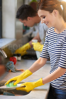 Buy stock photo Shot of a happy young couple cleaning their kitchen together
