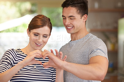 Buy stock photo Shot of an affectionate young couple bonding in their kitchen at home