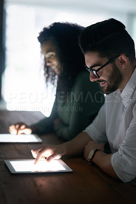 Buy stock photo Cropped shot of two colleagues working late on their digital tablets in an office