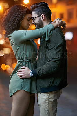 Buy stock photo Shot of a happy young couple embracing outdoors at night