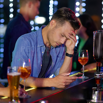 Buy stock photo Shot of an upset looking young man reading a text on his cellphone while sitting at the counter of a nightclub