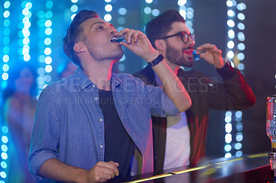 Buy stock photo Shot of two guys drinking shot at the bar counter in a nightclub