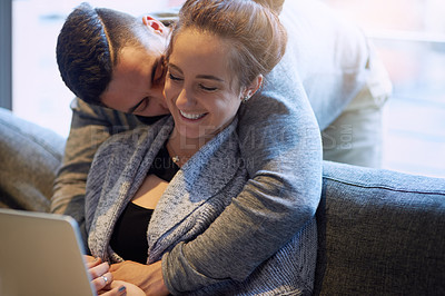 Buy stock photo Shot of an affectionate young couple surfing the net while relaxing on the sofa at home