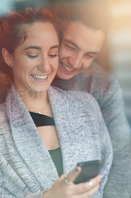 Buy stock photo Shot of an affectionate young couple looking at a cellphone while relaxing on the sofa at home