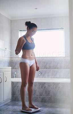 Buy stock photo Shot of a young woman weighing herself
