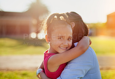 Buy stock photo Portrait of a smiling little girl hugging her mother while enjoying a day together in the park