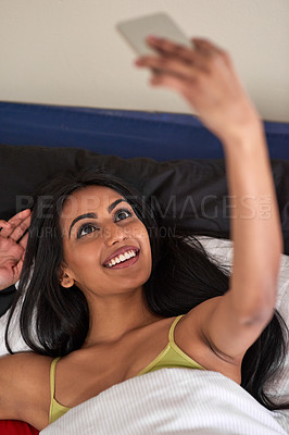Buy stock photo Shot of a happy young woman relaxing in bed and using her phone to take a selfie