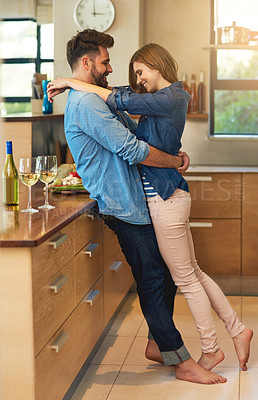 Buy stock photo Shot of an affectionate young couple sharing a romantic moment in the kitchen at home