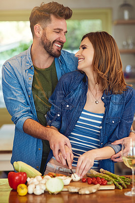Buy stock photo Shot of a happy young couple preparing a healthy meal together at home