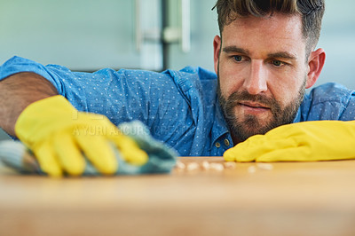 Buy stock photo Shot of a man wearing rubber gloves while wiping a table at home