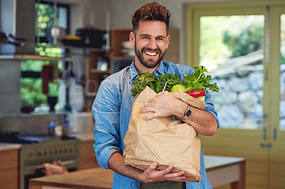 Buy stock photo Portrait of a happy man holding a bag full of healthy vegetables at home