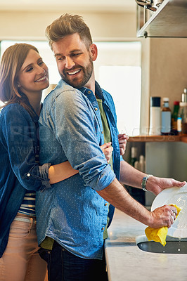 Buy stock photo Portrait of a young happy woman hugging her husband while he washes the dishes at home