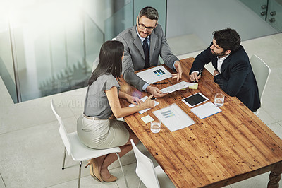 Buy stock photo Shot of three colleagues sitting around a meeting tablet in the office