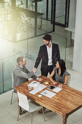 Buy stock photo Shot of two businessmen shaking hands during a meeting in the office