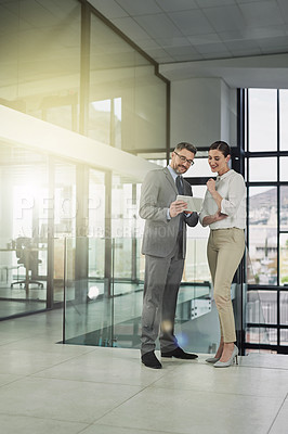 Buy stock photo Shot of two businesspeople looking over a tablet in the office