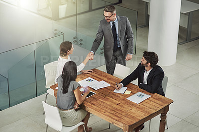 Buy stock photo Shot of two businesspeople shaking hands during a meeting in the office
