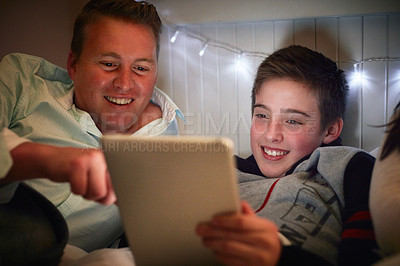 Buy stock photo Cropped shot of a father and son using a digital tablet together at night