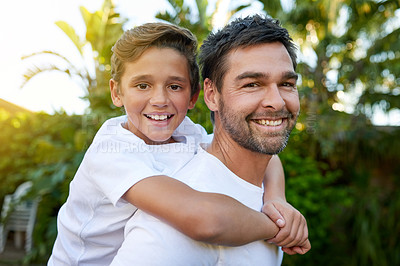 Buy stock photo Portrait of a father carrying his son on his back outside