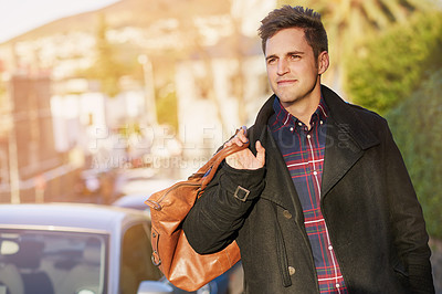 Buy stock photo Shot of a handsome young man taking a walk through the city