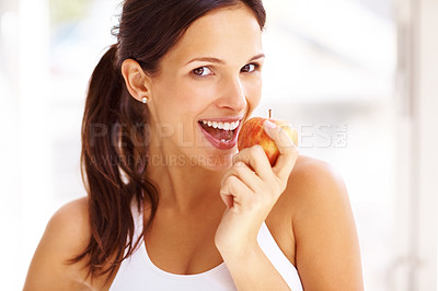 Buy stock photo Portrait of fit young girl biting a fresh ripe apple against bright background