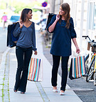 Happy young women walking on street with shopping bags