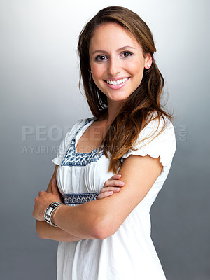 Buy stock photo Portrait of a cute young woman standing with her hand folded against grey background