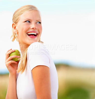 Buy stock photo Happy female eating a green apple with the blue sky as the background