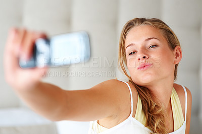 Buy stock photo Portrait of a lovely young female taking picture of herself through her cellphone