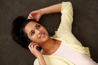 Buy stock photo Portrait of a beautiful young woman talking on her cellphone while lying on the floor