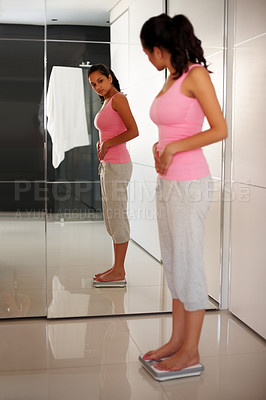 Buy stock photo Portrait of a cute young woman measuring her weight while standing on weighing machine