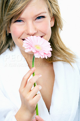 Buy stock photo Young woman holding a flower, smelling it and smiling, portrait