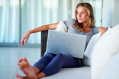 Buy stock photo Portrait of a pretty young woman looking away while working on laptop