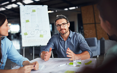 Buy stock photo Shot of a mature manager talking to his team while sitting around a table in an office