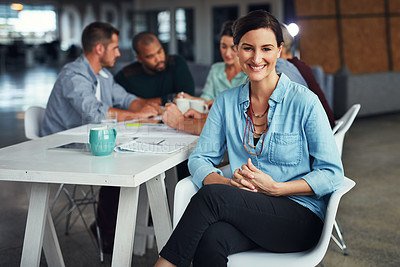 Buy stock photo Portrait of a young woman sitting at a table in an office with colleagues working in the background