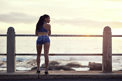 Buy stock photo Rearview shot of a fit young woman looking at the view during a workout outdoors