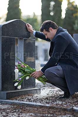 Buy stock photo Shot of a young man visiting a gravesite with a bunch of flowers