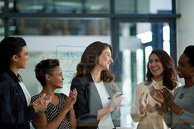 Buy stock photo Shot of a group of businesswomen working on a glass wall during a meeting