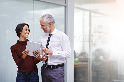 Buy stock photo Shot of two colleagues looking at a tablet together in the office