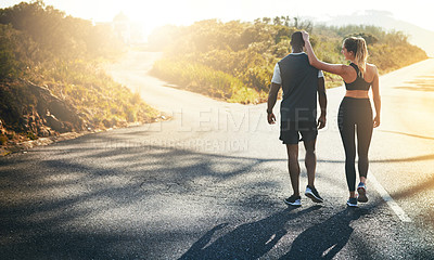 Buy stock photo Shot of a fit young couple slowing down for a walk during their run outdoors