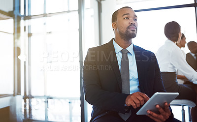 Buy stock photo Shot of a thoughtful young businessman using a digital tablet during a meeting at work