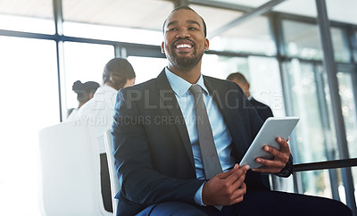 Buy stock photo Shot of a happy young businessman using a digital tablet during a meeting at work